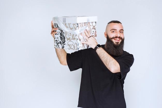 Homme à la barbe tenant un coffret cadeau bleu blanc souriant et se sentant heureux.