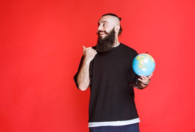 Homme à la barbe tenant un globe et pointant vers quelque part.