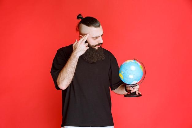 Homme à la barbe tenant un globe terrestre et à la recherche d'endroits dessus.