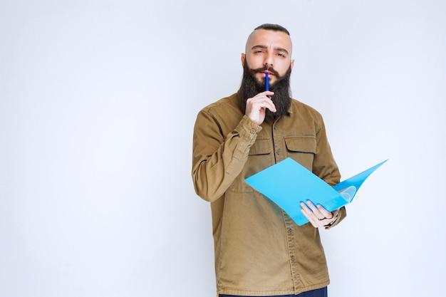 Homme à la barbe tenant un questionnaire et a l'air confus et réfléchi.