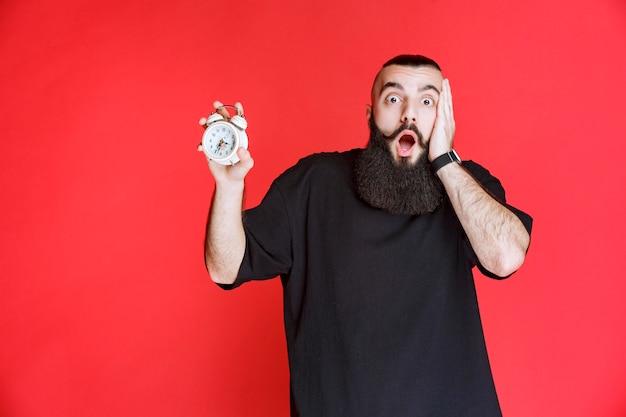Homme à la barbe tenant un réveil et terrifié car il est en retard.