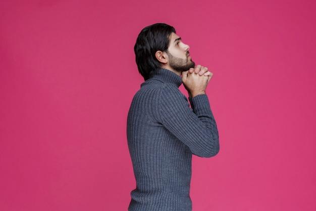 Homme à la barbe tenant ses mains d'une manière comme s'il prie ou souhaite quelque chose.
