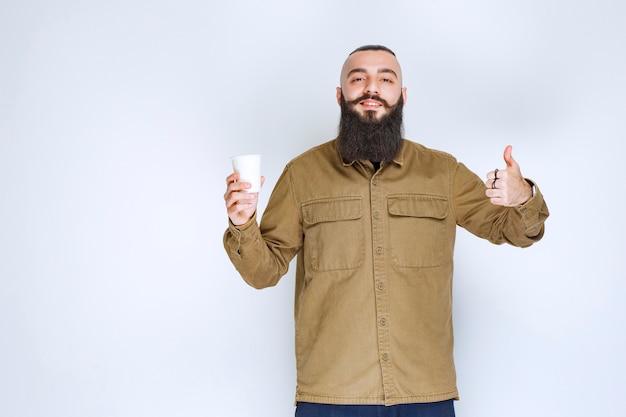 Homme à la barbe tenant une tasse de café et appréciant le goût.