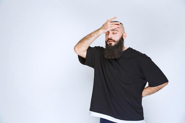 Homme avec barbe tenant la tête car il a mal à la tête.