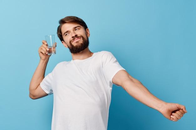 Homme à la barbe tenant un verre d'eau à la main