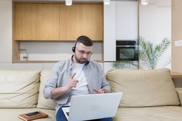 Un homme avec une barbe travaille à domicile assis sur le canapé utilise un ordinateur portable et un casque avec un microphone mène une consultation en ligne