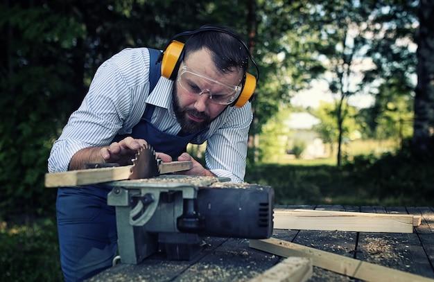 Homme de barbe de travailleur avec la scie circulaire