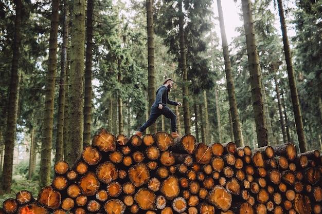 Homme avec une barbe va sur le bois dans la forêt