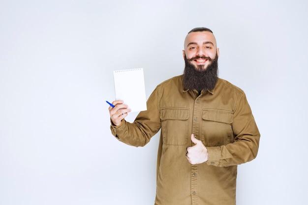 Homme à la barbe vérifiant la liste des projets et a l'air satisfait.