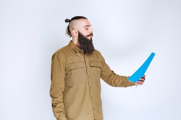 Homme à la barbe vérifiant la liste des projets et marquant des notes ou des corrections.