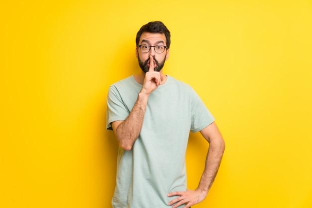 Homme, à, barbe, et, vert, chemise, montrer signe, de, geste silence, mettre doigt, dans bouche