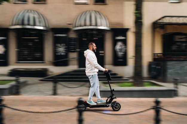 Un homme avec une barbe en vêtements blancs se promène rapidement dans la ville sur un scooter électrique.