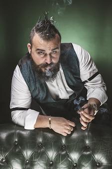 Homme à la barbe, vêtu d'un costume et d'un noeud papillon, regardant la caméra en fumant.