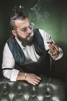Homme à la barbe, vêtu d'un costume et d'un noeud papillon, regardant un cigare en fumant.