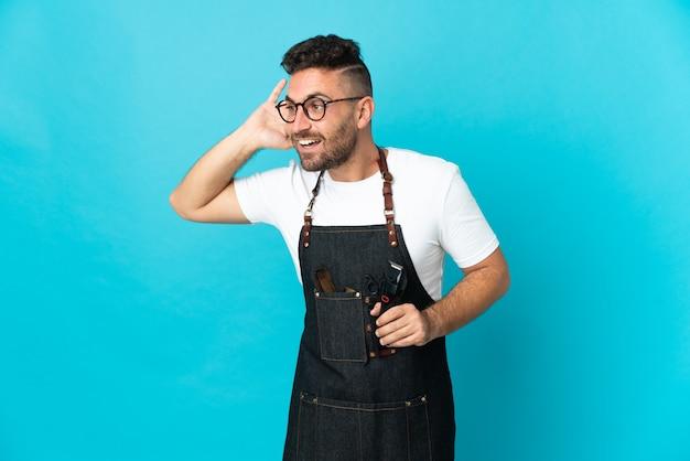 Homme de barbier dans un tablier écoutant quelque chose en mettant la main sur l'oreille