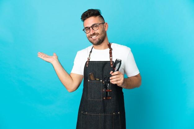 Homme de barbier dans un tablier étendant les mains sur le côté pour inviter à venir