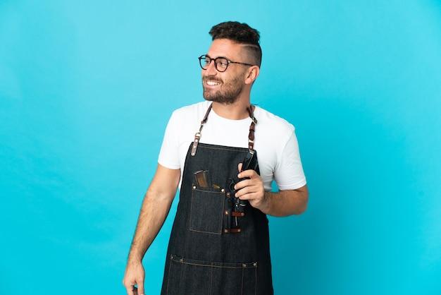 Homme de barbier dans un tablier regardant sur le côté et souriant