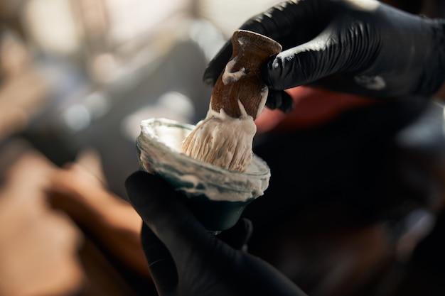 Homme barbier mains mousser la crème à raser avec brosse