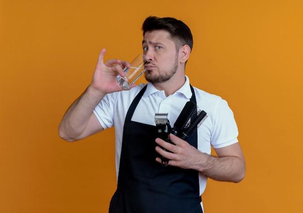 Homme barbier en tablier tenant une brosse à cheveux et tondeuse à barbe eau potable regardant la caméra avec une expression sceptique debout sur fond orange