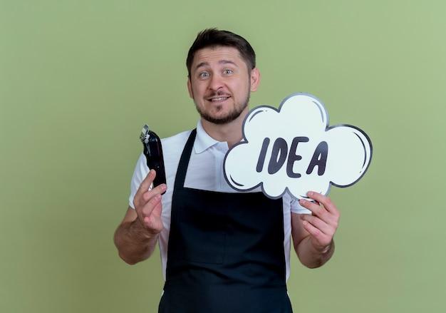 Homme de barbier en tablier tenant tondeuse à barbe et mot d'idée de signe de bulle discours avec visage heureux debout sur le mur vert