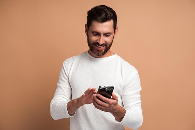 Homme barbu affirmé regardant attentivement l'affichage du smartphone qu'il tient, surfant sur internet, faisant des achats en ligne. studio intérieur tourné isolé sur fond beige