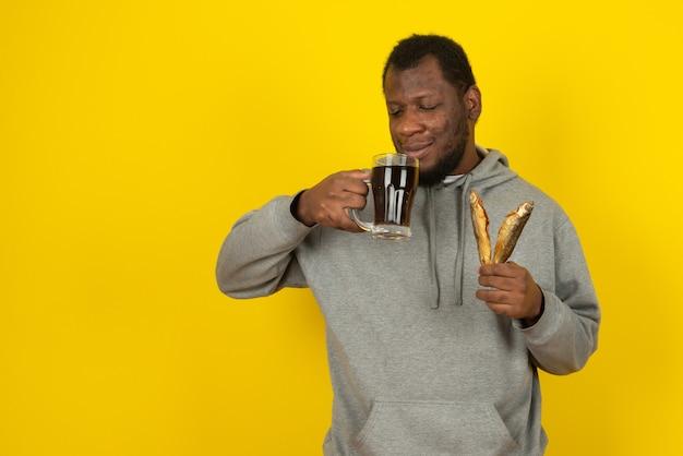 Un homme barbu afro-américain avec une bière noire dans une main et un poisson dans l'autre, se dresse sur un mur jaune.