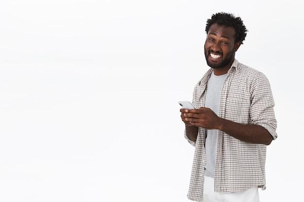 Homme barbu afro-américain gai et drôle en tenue décontractée, tenant un smartphone