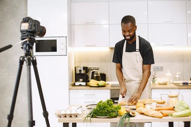 Homme barbu afro-américain souriant et cuisinant. vidéo de tournage d'un blogueur pour cuisiner un vlog dans la cuisine à la maison. homme portant un tablier.