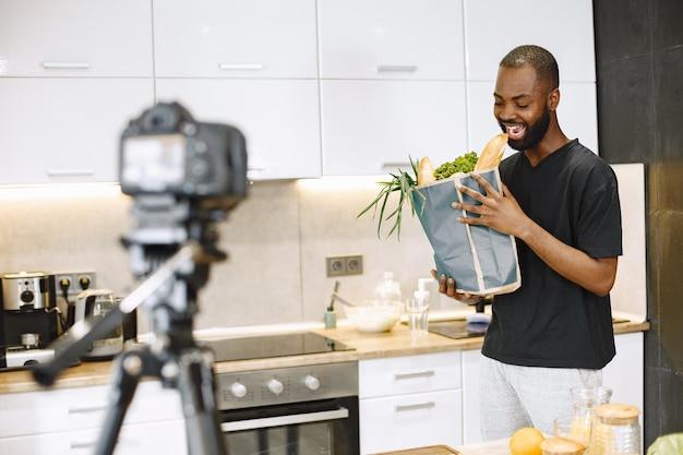 Homme barbu afro-américain souriant et tenant un paquet avec de la nourriture
