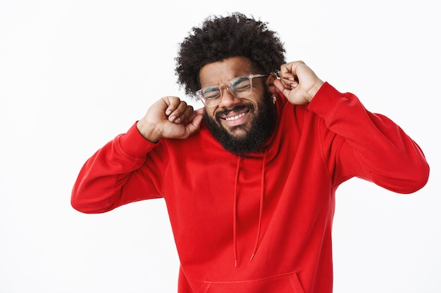 Homme barbu afro-américain en sweat à capuche rouge grimaçant, ferme les yeux intenses et serrant les dents comme se préparant à un bruit fort ou au son de la sirène, fermant les oreilles sans entendre un coup ennuyeux sur un mur gris