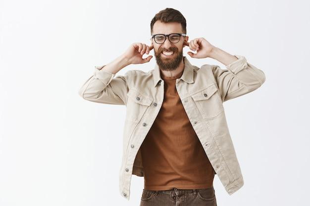 Homme barbu agacé et déçu dans des verres posant contre le mur blanc