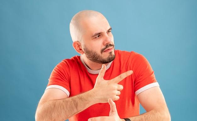 Un homme barbu d'âge moyen dans un t-shirt rouge sur fond bleu regarde joyeusement sur le côté. ses mains sont sur son visage. fermer. isolé.