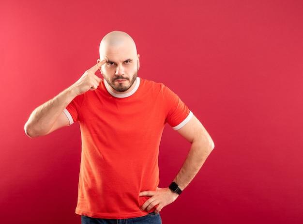 Un homme barbu d'âge moyen dans un t-shirt rouge sur fond rouge montre sa main une arme à feu sur sa tempe. isolé.