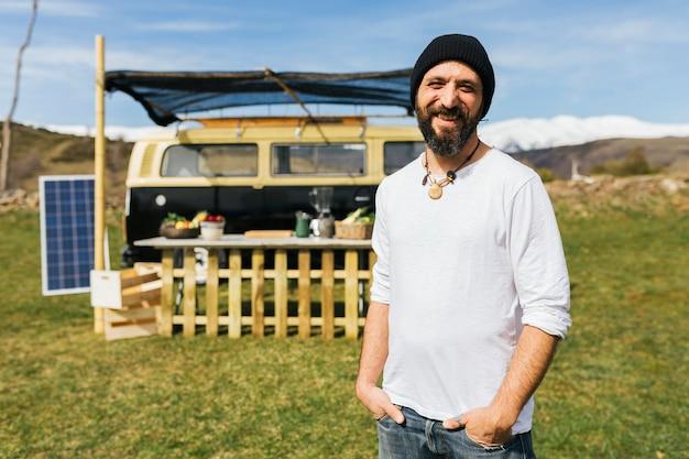 Homme barbu d'âge moyen en face d'un camion de nourriture van sur un champ