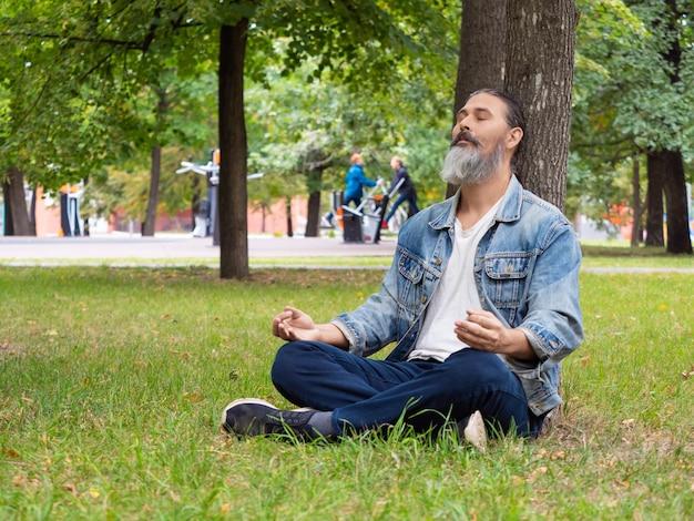 Un homme barbu d'âge moyen faisant une pause dans l'agitation de la ville qu'il médite en t...