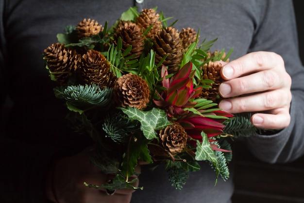 Homme barbu d'âge moyen tenant un bouquet d'hiver de brindilles de sapin nobil, cônes, pistache, leucodendron et lierre, concept de cadeau d'hiver