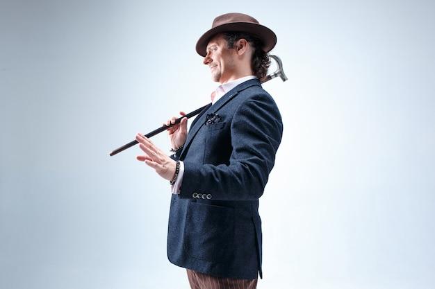L'homme barbu d'âge mûr en costume et chapeau tenant la canne. isolé sur un gris.