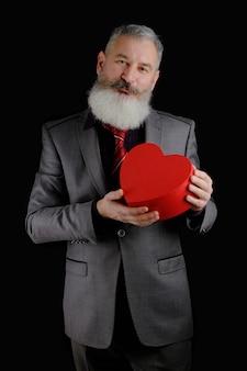 Homme barbu d'âge mûr porter un costume gris détient une boîte-cadeau en forme de coeur rouge, fond noir isolé