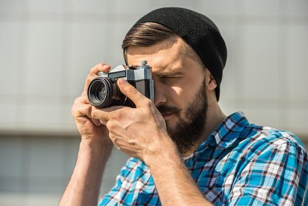 Homme barbu avec appareil photo vintage fait une photo.