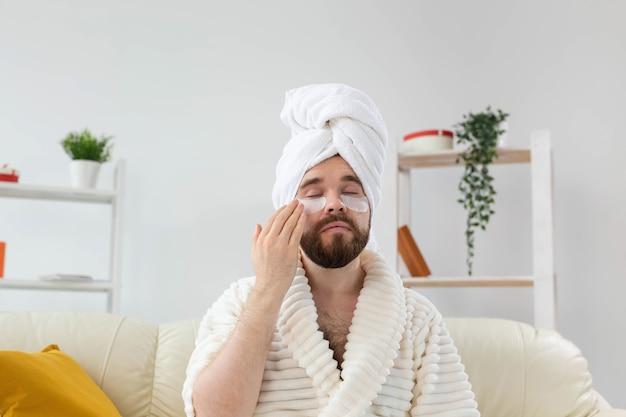 Homme barbu appliquant des cache-œil sur son visage. rides et soins du visage à domicile pour hommes.