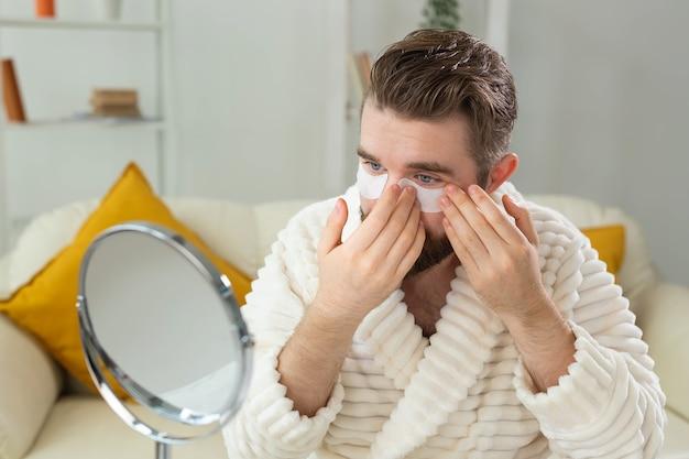 Homme barbu appliquant des patchs oculaires sur ses rides du visage et soins du visage à domicile pour hommes