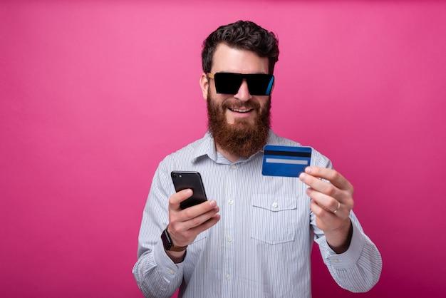 Homme barbu appréciant les achats en ligne ou les services bancaires sur internet tenant son téléphone et sa carte de crédit sur fond rose.