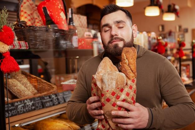 Homme barbu appréciant l'odeur du délicieux pain frais.