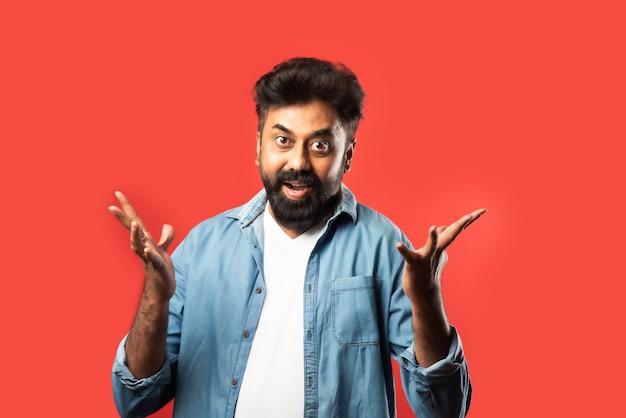 Homme barbu asiatique indien avec des regards surpris ou wow, debout sur le rouge