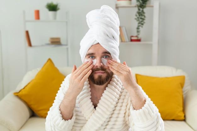Homme barbu assis avec des cache-œil sur ses rides du visage et soins du visage à domicile pour hommes