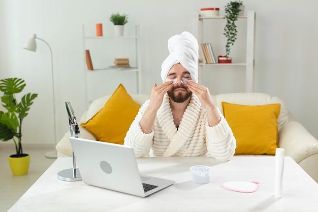Homme barbu assis avec des cache-œil sur son visage. rides et soins du visage à domicile pour hommes.