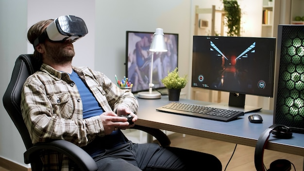 Homme barbu assis sur une chaise de jeu jouant à des jeux à l'aide d'un casque vr. femme en arrière-plan.