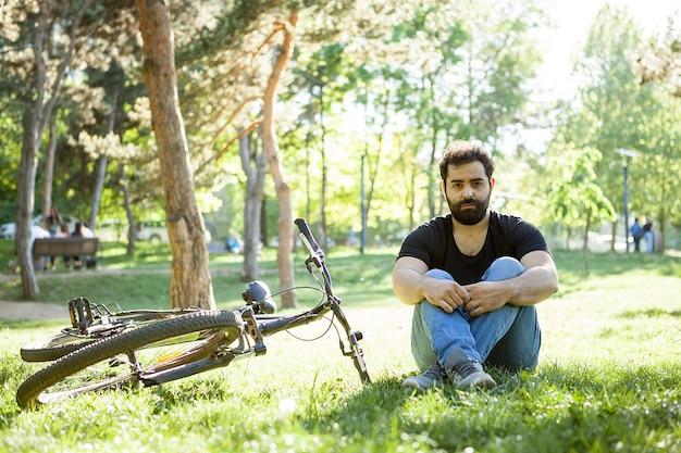 Homme barbu assis à côté de son vélo sur le sol dans le parc