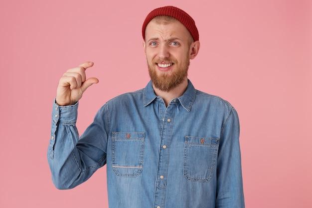 Un homme barbu au chapeau rouge drôle porte une chemise en jean, fait un geste de la main, montre quelque chose de très petit, pose contre le mur rose. un étudiant perplexe montre tout ce qu'il a appris