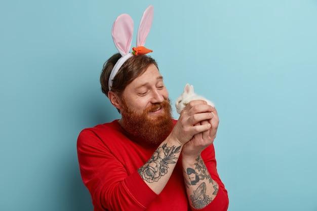 Un homme barbu au gingembre bienveillant joue avec un petit lapin mignon, porte des oreilles de lapin et un pull rouge, célèbre pâques, apprécie le printemps, pose à l'intérieur. concept de traditions et de fêtes religieuses